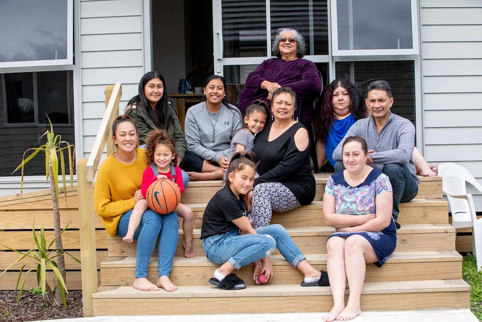 The Tawhai whānau in front of their new whare. Photo credit: Josie McClutchie.